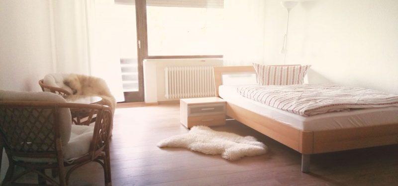 Ein Zimmer mit Bett,Stühlen und einem Bettvorleger